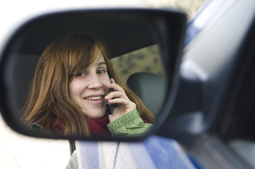 Teen girl talking on a cell phone in a car