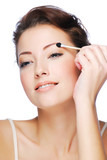 applying eyeshadow using cosmetic applicator poster
