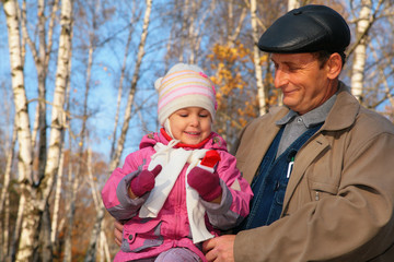 Portrait of grandfather with granddaughter in wood in autumn .