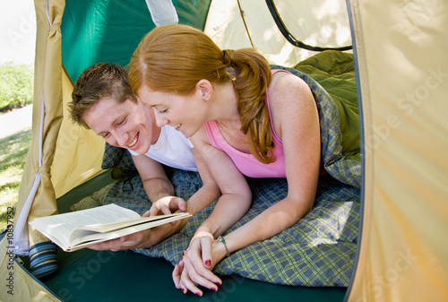 Couple laying in tent reading book