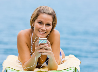 Woman listening to mp3 player at beach