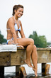 Woman sitting on pier at lake
