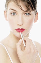 Young Woman face making-up with a lipstick, close-up (studio)