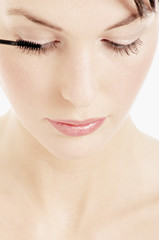 Young Woman face making-up with mascara, close-up (studio)
