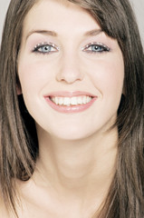 Young Woman face with make up, smiling, looking at he camera, close-up (studio)