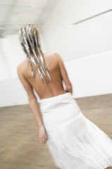 Young woman with hair mask, view from the back, white skirt, blurred motion