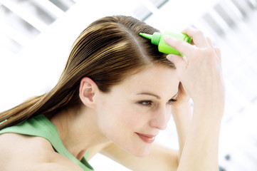 Portrait of a young woman pouring on hair lotion on her head