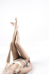 Woman in lingerie lying on floor, legs aloft, close up (studio)