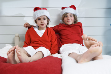 2 boys on bed, disguised as Santa Claus