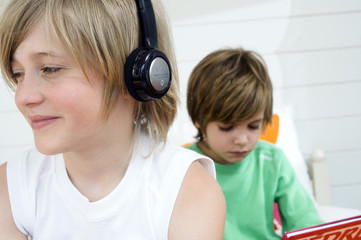 2 boys at home, one wearing headphones, the other reading in background
