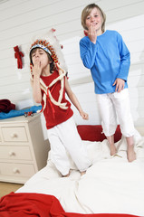 2 boys playing indians standing onbed