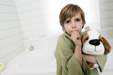 Little boy sucking his thumb, holding stuffed dog