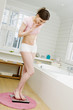 Young woman on scales in bathroom, hand over mouth