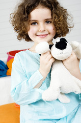 Little girl holding stuffed dog
