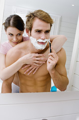 Couple embracing in bathroom, barechested man shaving in front of mirror
