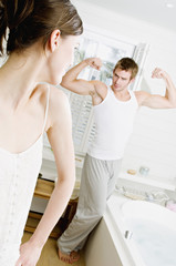 Couple in bathroom, woman watching man flexing muscles