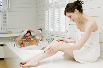 Couple in bathroom, man having a bath and woman wrapped in a towel shaving her legs