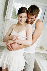 Smiling couple embracing in bathroom, looking at pregnancy test