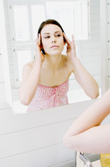 Young woman in front of bathroom mirror