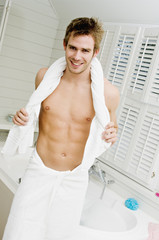 Barechested man standing in a bathroom, wrapped in a towel, smiling for the camera