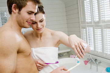 Couple in a bathroom squeezing toothpaste onto toothbrushes