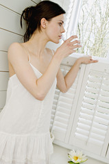 Young woman in white robe drinking glass of water, looking through window
