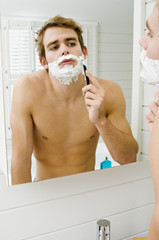 Barechested man shaving in front of bathroom mirror