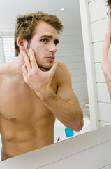 Barechested man in front of bathroom mirror