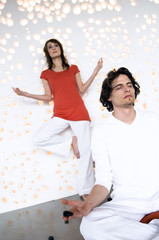 Couple in yoga position, man sitting cross-legged, woman standing in background