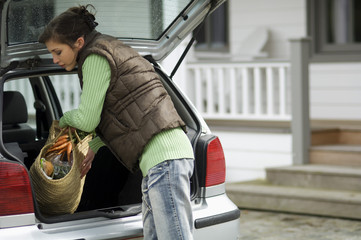 Young woman taking a shopping basket out of a car trunk