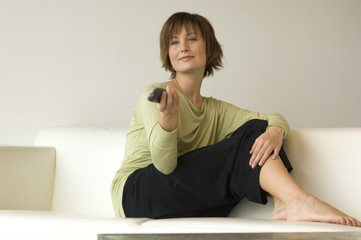 Young woman sitting on a sofa using remote-control