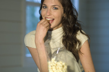 Portrait of a woman eating popcorn, smiling for the camera