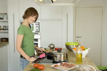 Young woman cooking, looking at the camera