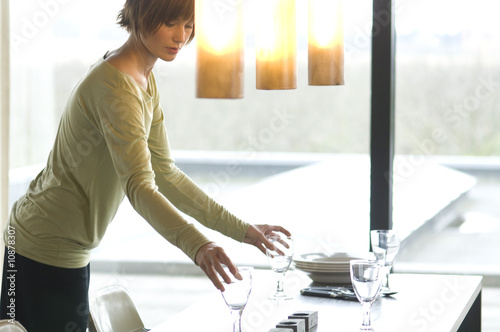 Young woman setting the table