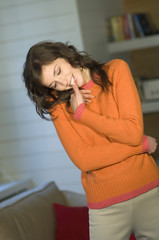 Young smiling woman, with finger in her mouth, orange sweater