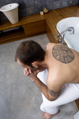 Tattooed man, barechested, sitting on tub edge, elevated view