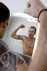 Tattooed man flexing muscles in front of bathroom mirror