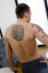 Tattooed man, barechested, standing in the bathroom, rear view