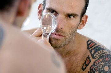 Tattooed man, barechested, looking in bathroom mirror, holding a magnifying glass