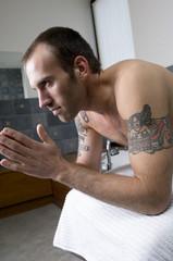 Tattooed man, barechested, sitting on tub edge