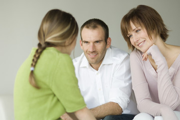 Couple and little girl talking, sitting in living-room
