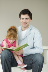 Man and little girl reading children's book