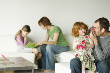 Couple and 2 little girls sitting in the living-room