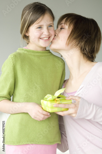 Woman holding present, kissing little girl on her cheek