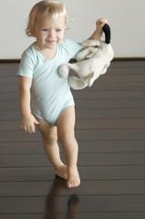 Little boy holding stuffed dog, walking on wooden floor, front view