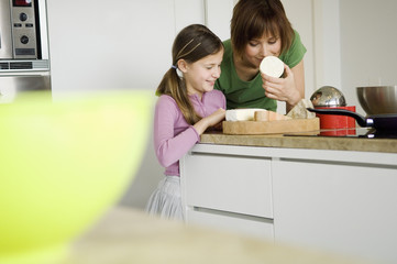 Woman and little girl in the kitchen, preparing cheese tray