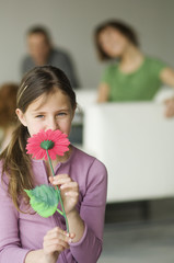 Little girl holding a plastic flower in front of her face, couple in the background