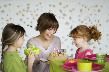 Woman and 2 little girls with birthday cake