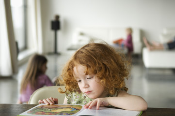 Little girl reading children's book