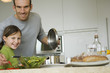 Man and little girl cooking, smiling for the camera